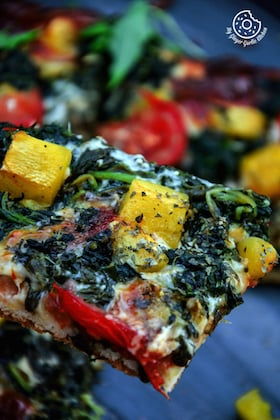 Image of Garlicky Spinach Mango Tomato Pizza with Hot Pepper Sauce and Flakes