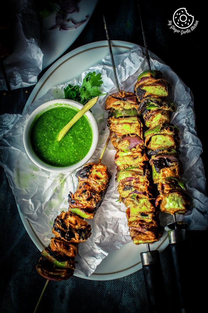 Tandoori paneer tikka served in white plate with some green coriander chutney
