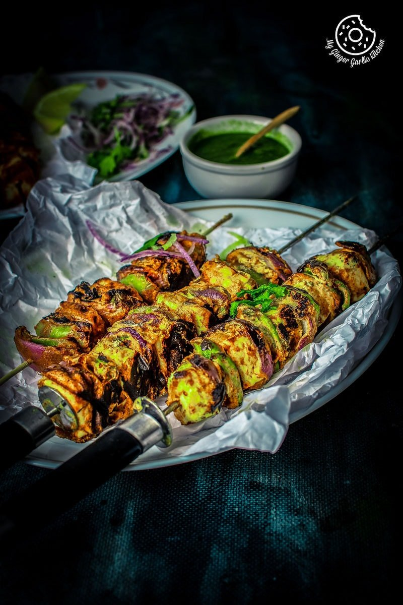 Paneer Tikka skewers serves in a white tray and a chutney bowl in background