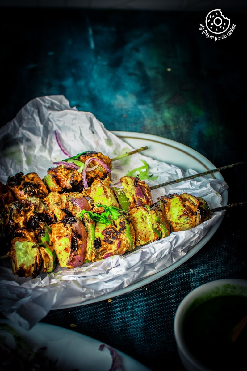 Paneer tikka topped with coriander leaves served in a plate
