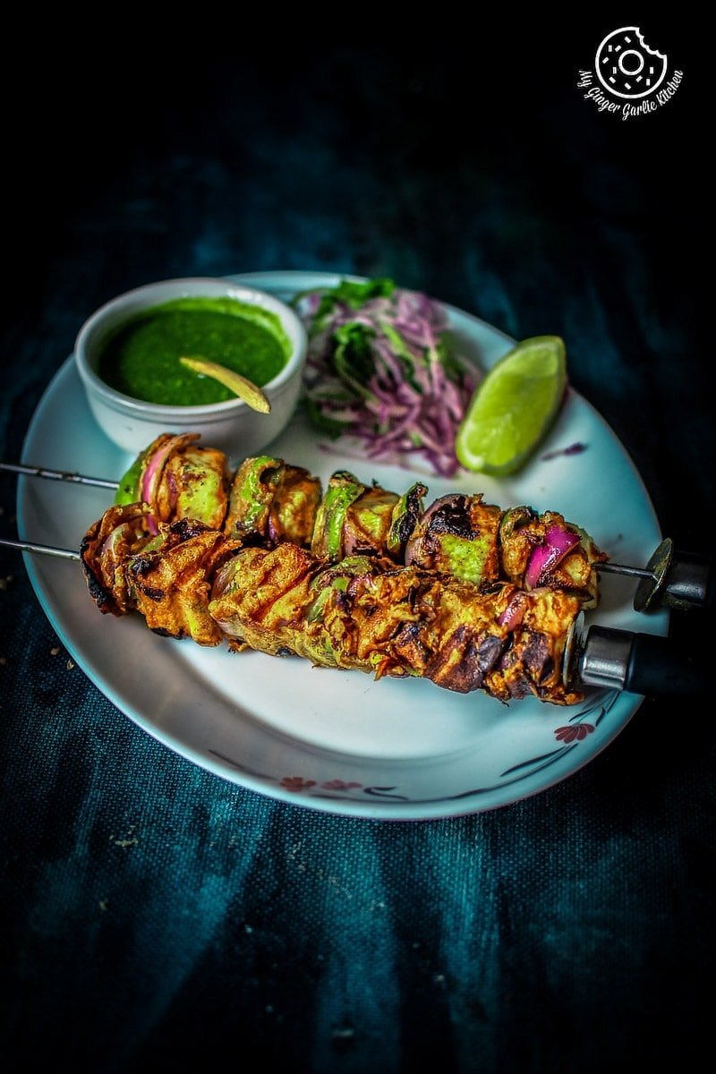 paneer tikka served in a plate with some green coriander chutney and onion slices