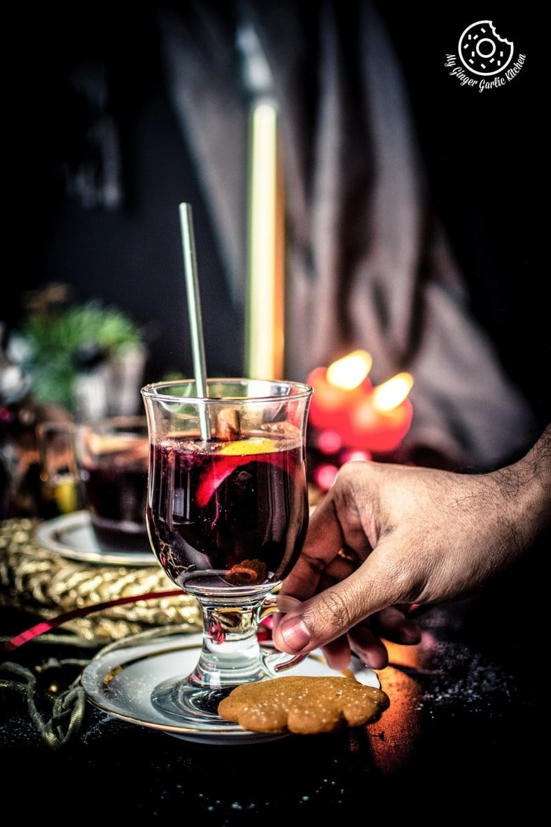 a male hand holding a glass of mulled wine