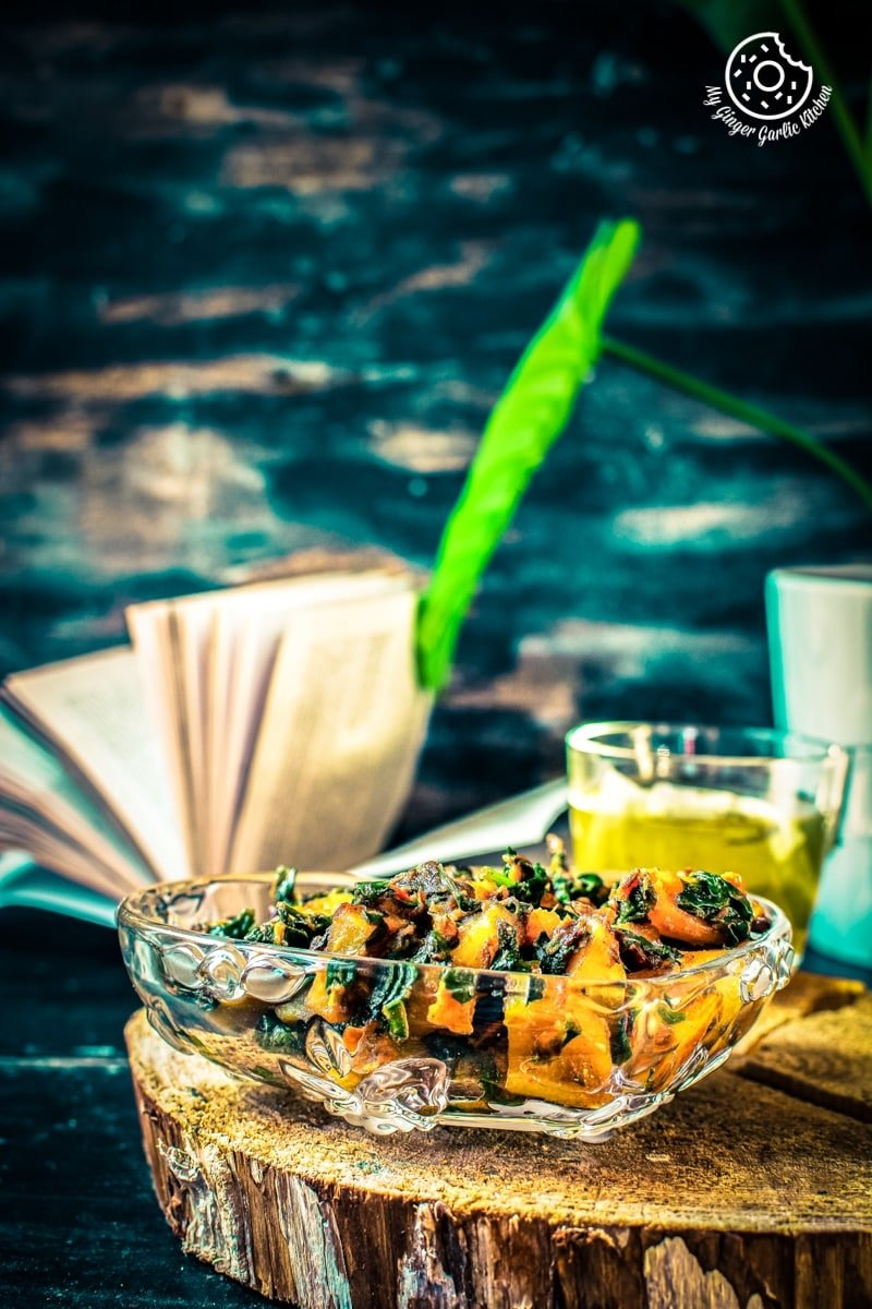a glass bowl of aloo palak kept on a wooden log and a book in backdrop