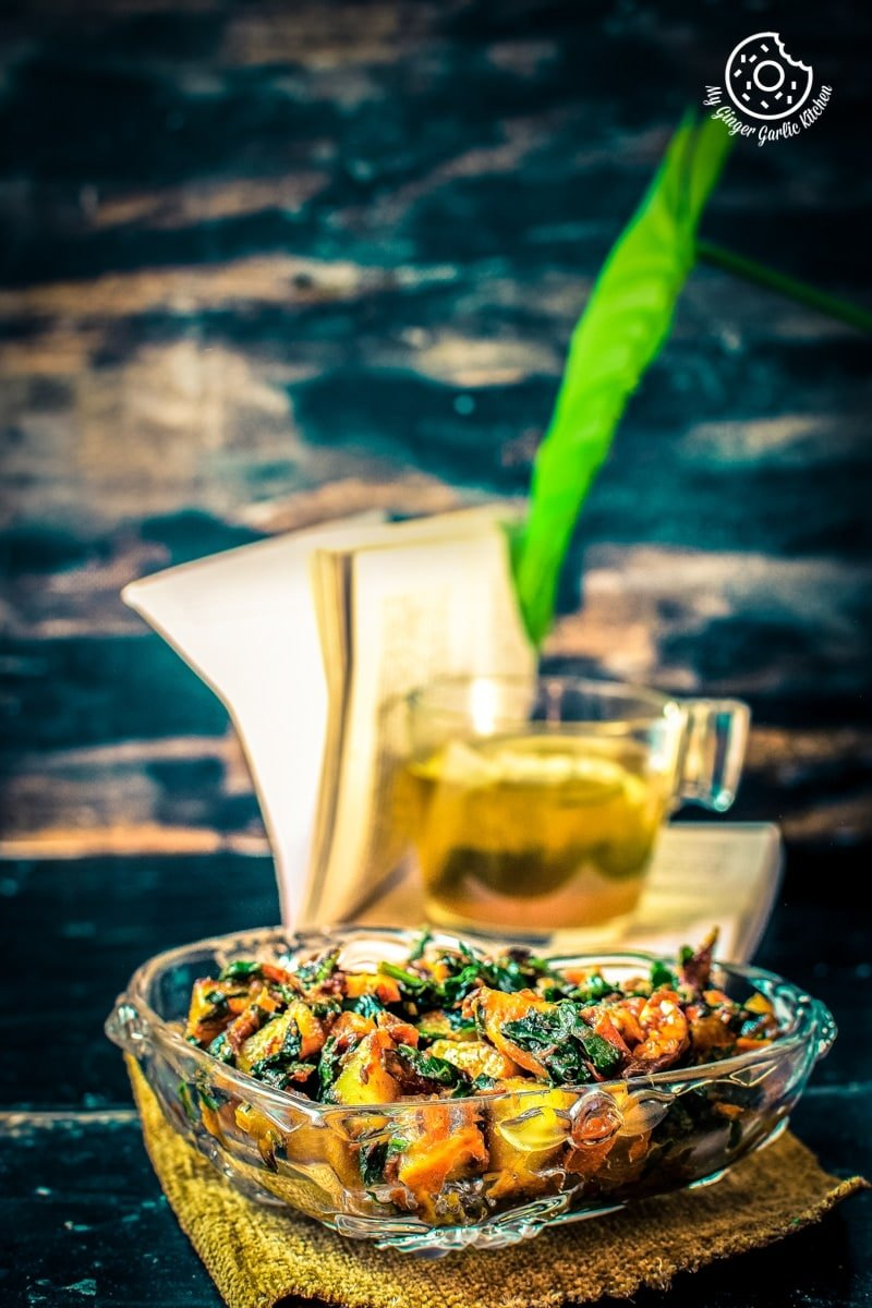 a glass bowl of aloo palak kept on a brown wooden log and a transparent tea cup in background
