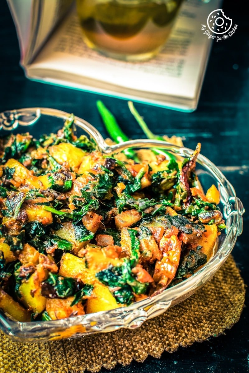aloo palak served in a glass bowl on brown mat
