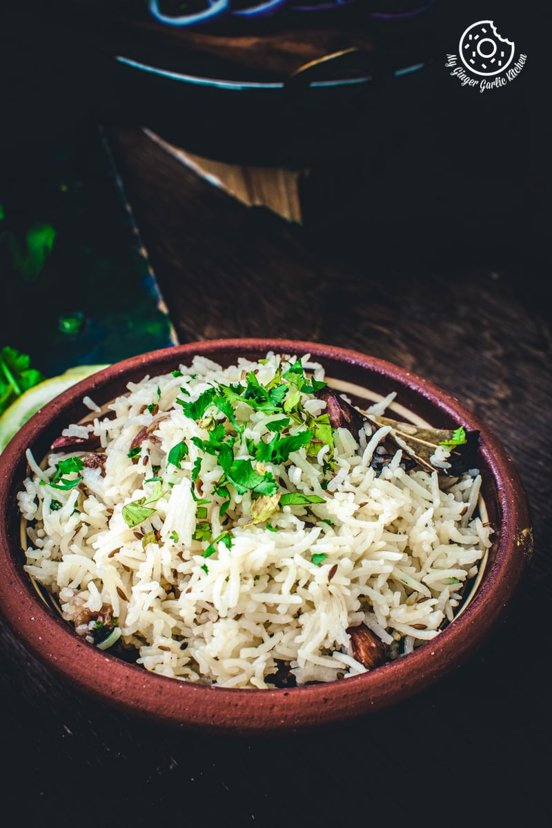 jeera rice served in a brown earthy bowl on a dark brown background