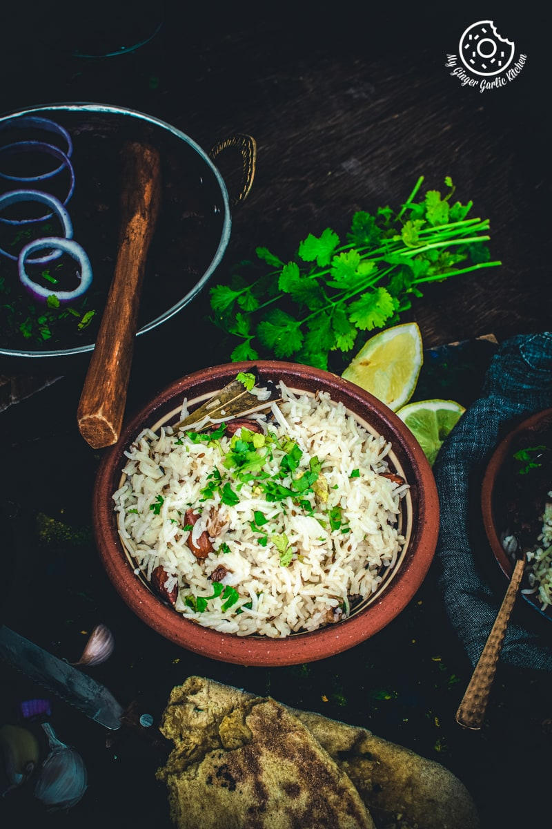 a bowl of indian cumin rice with some coriander leaves and a wooden spoon