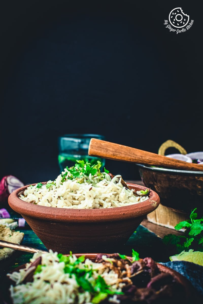 jeera rice bowl topped with fresh coriander leaves