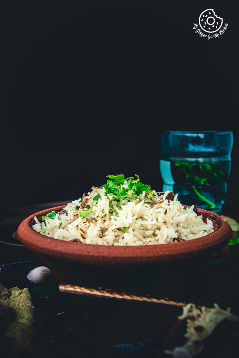 a brown bowl of cumin rice is sprinkled with some cumin powder and coriander leaves