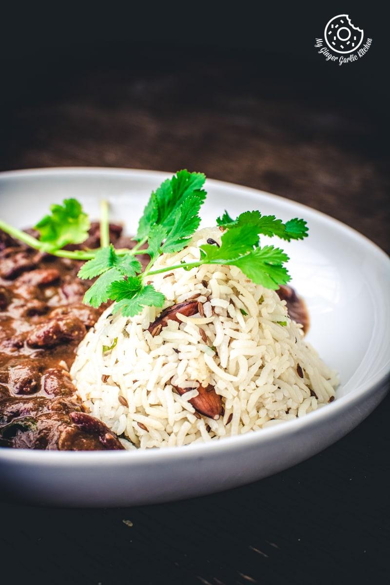 a close up shot of jeera rice and rajma garnished with a coriander stem