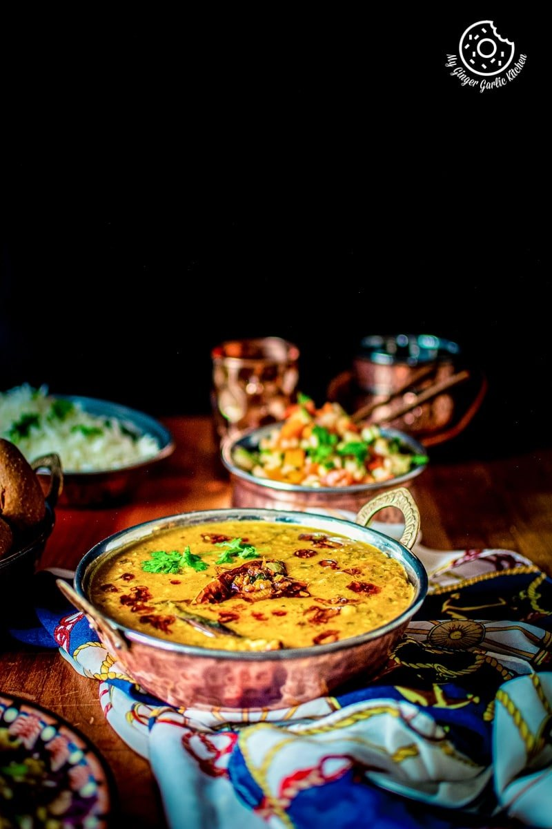 panchmel dal served in a copper kadahi and a copper salad bowl in backdrop