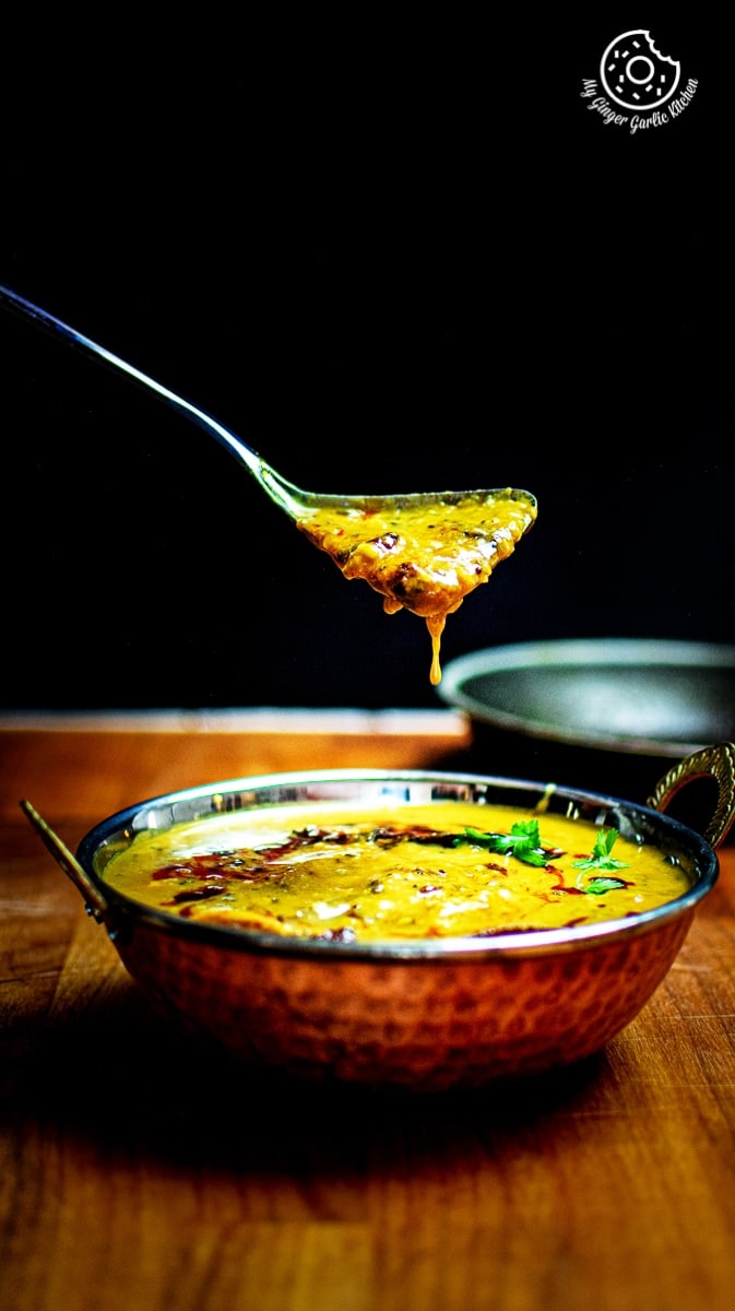panchmel dal dripping from a metal spoon