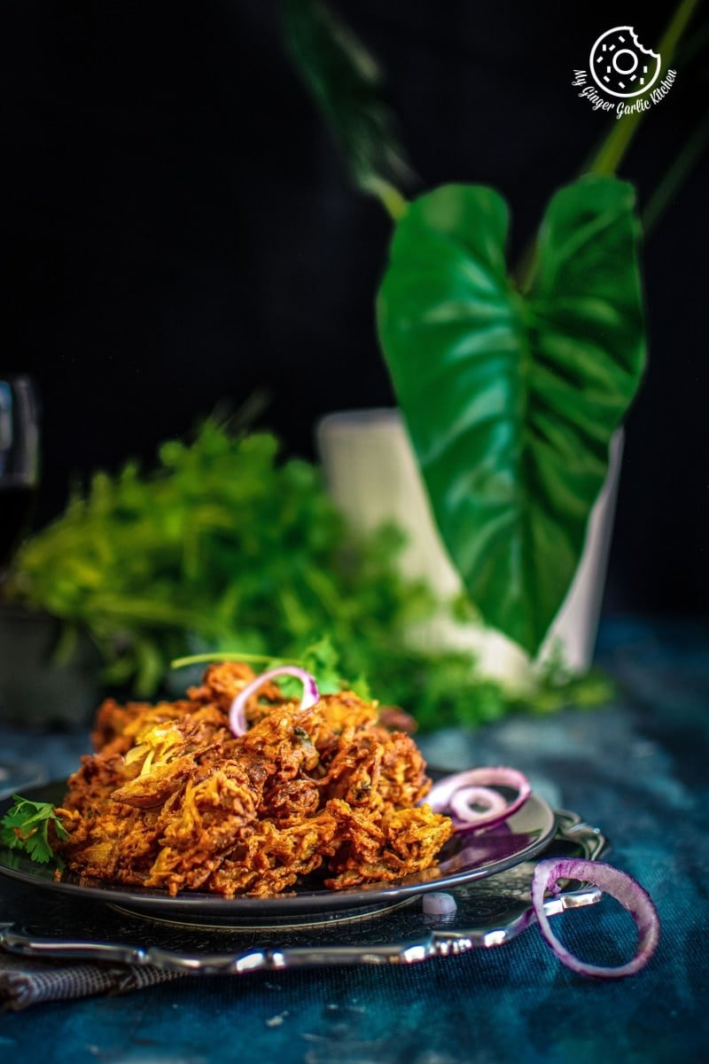 pyaaz pakora served in a dark grey plate with some onion rings and some leaves in the background