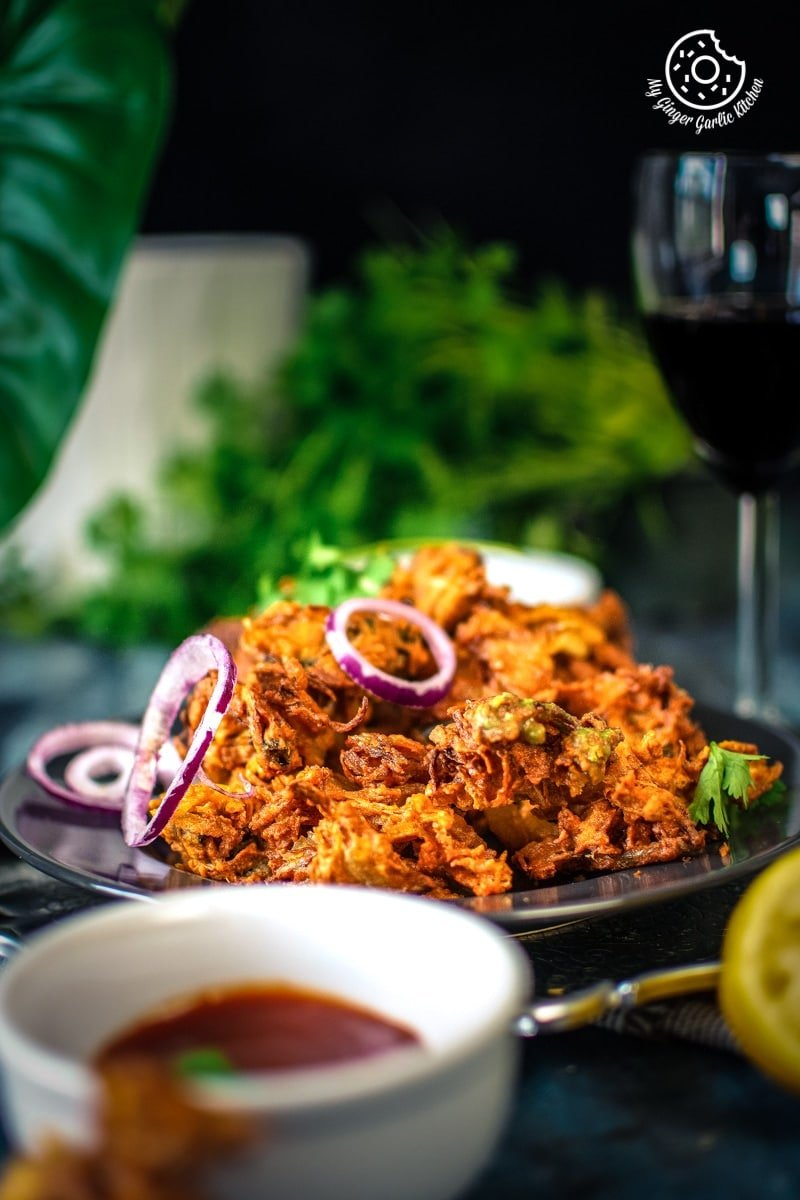 onion pakoda with purple onion rings and a wine glass in the backdrop