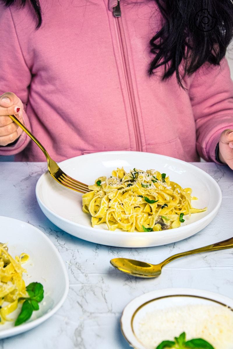 a kid holding a golden fork over fettccine alfredo plate
