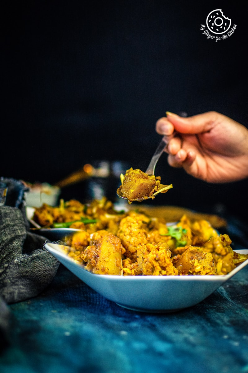 a hand holding a spoon filled with aloo gobi