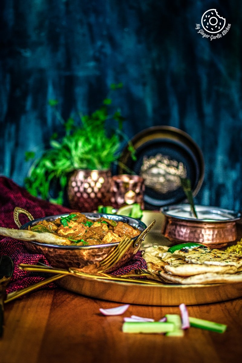 kadai paneer served in copper kadai with some garlic naan
