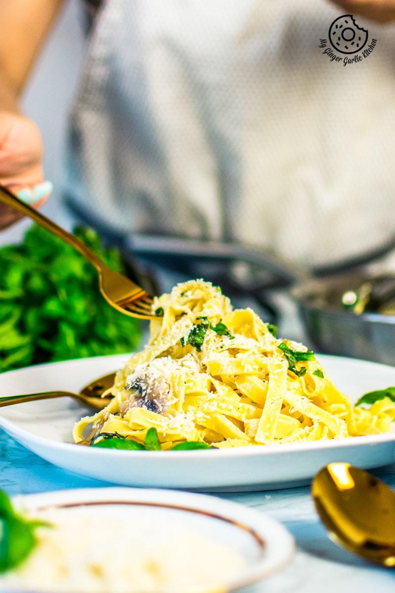 a golden fork is held over mushroom fettuccine plate