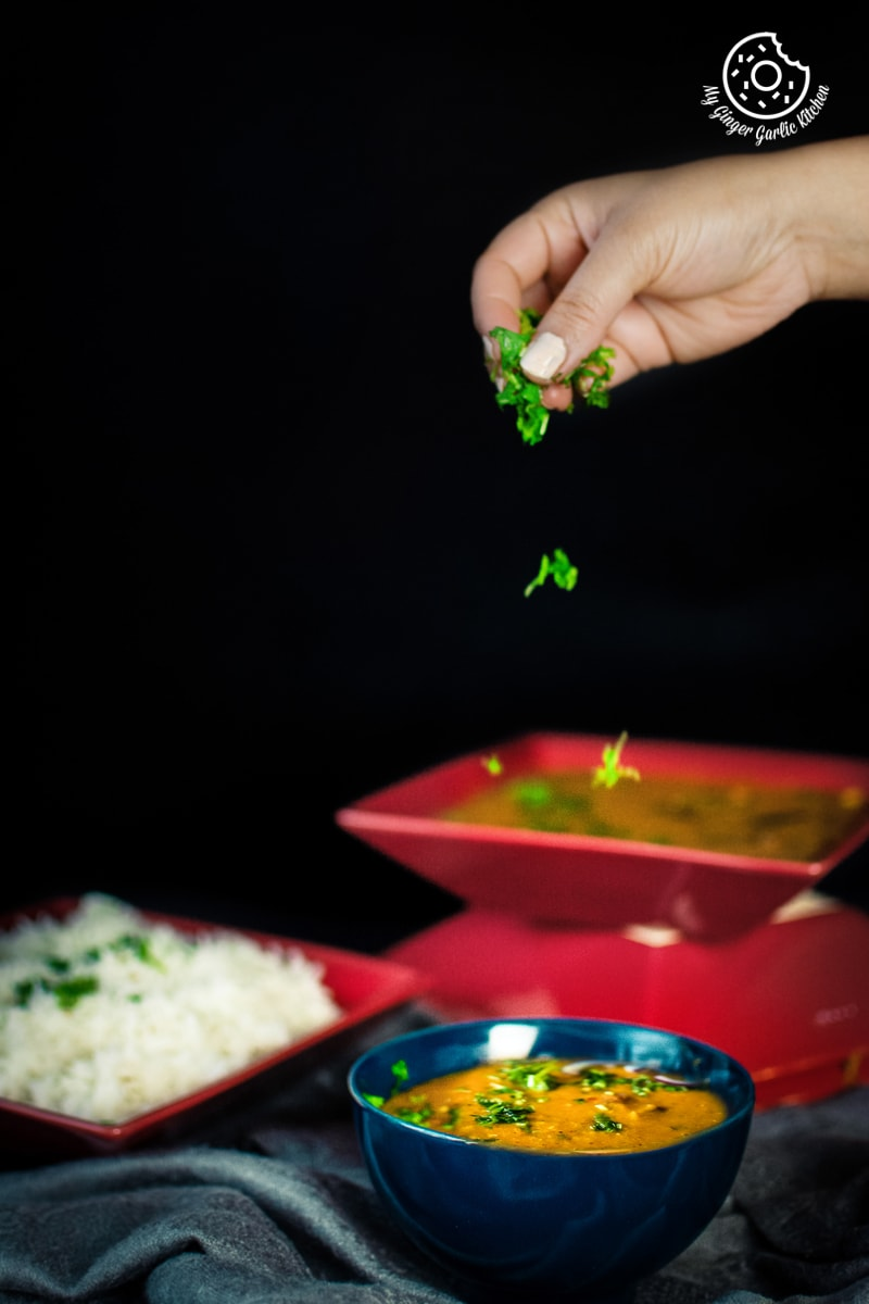 a hand sprinkling cilantro over masoor dal bowl