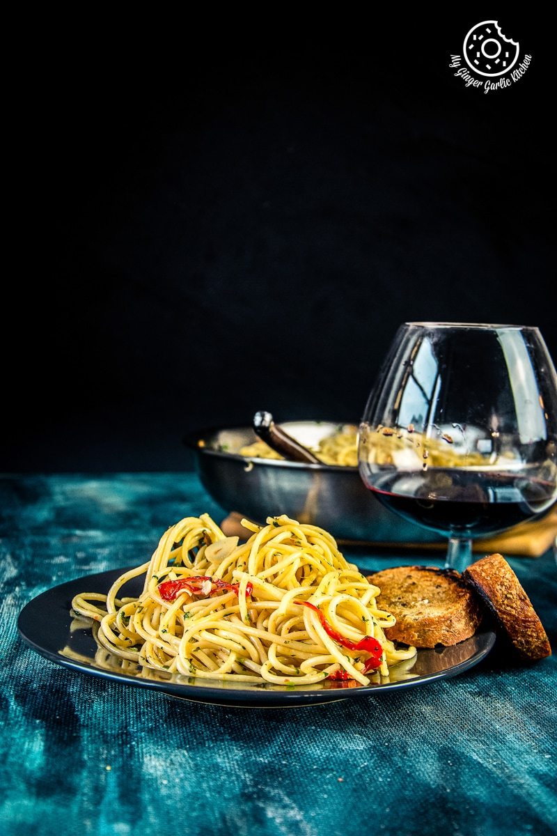 pasta aglio e olio served in grey plate along with toasted bread and wine glass