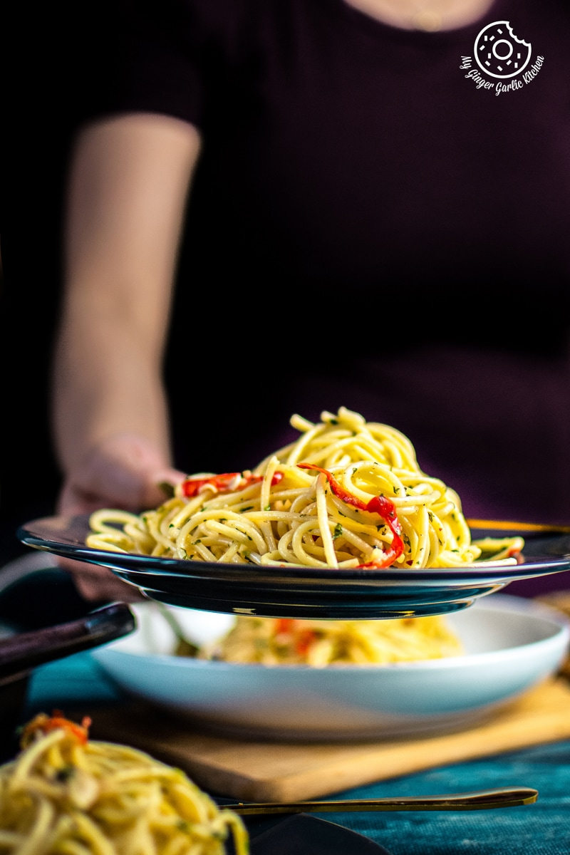 a female holding pasta aglio e olio served in a grey plate