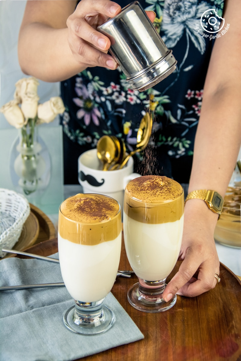 a female sprinkling cocoa powder on dalgona coffee glass
