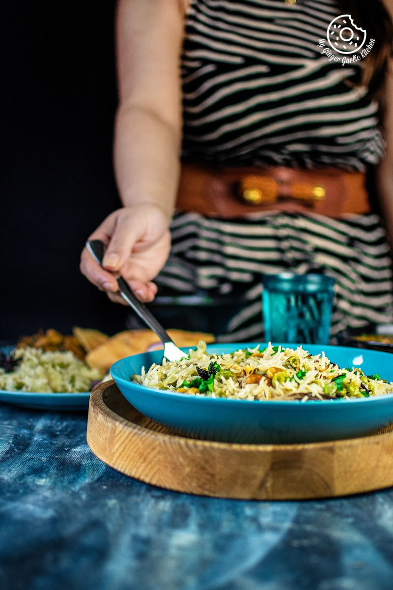 a female holding a spoon full of matar pulav served in a blue plate