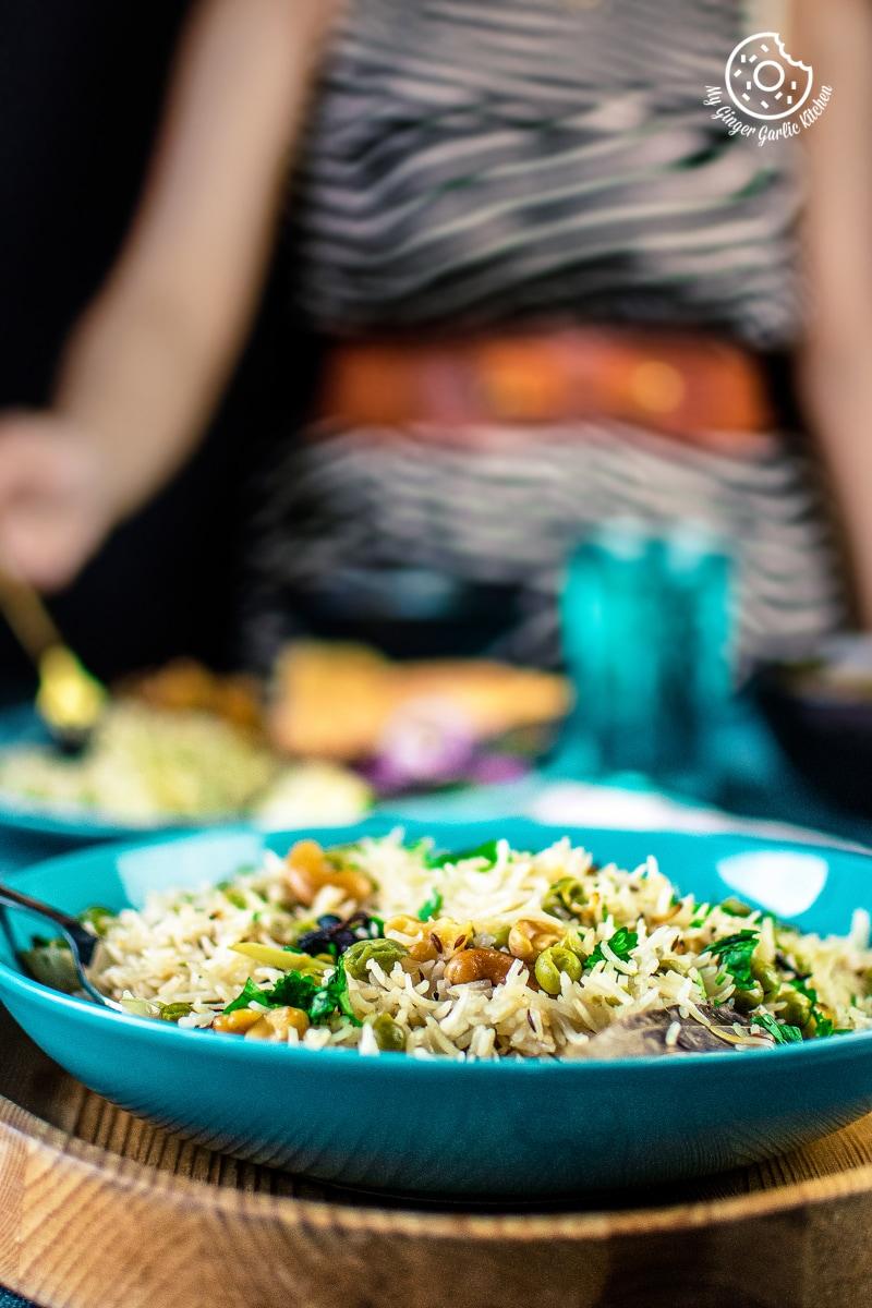 a closeup shot of matar pulao served in a blue plate
