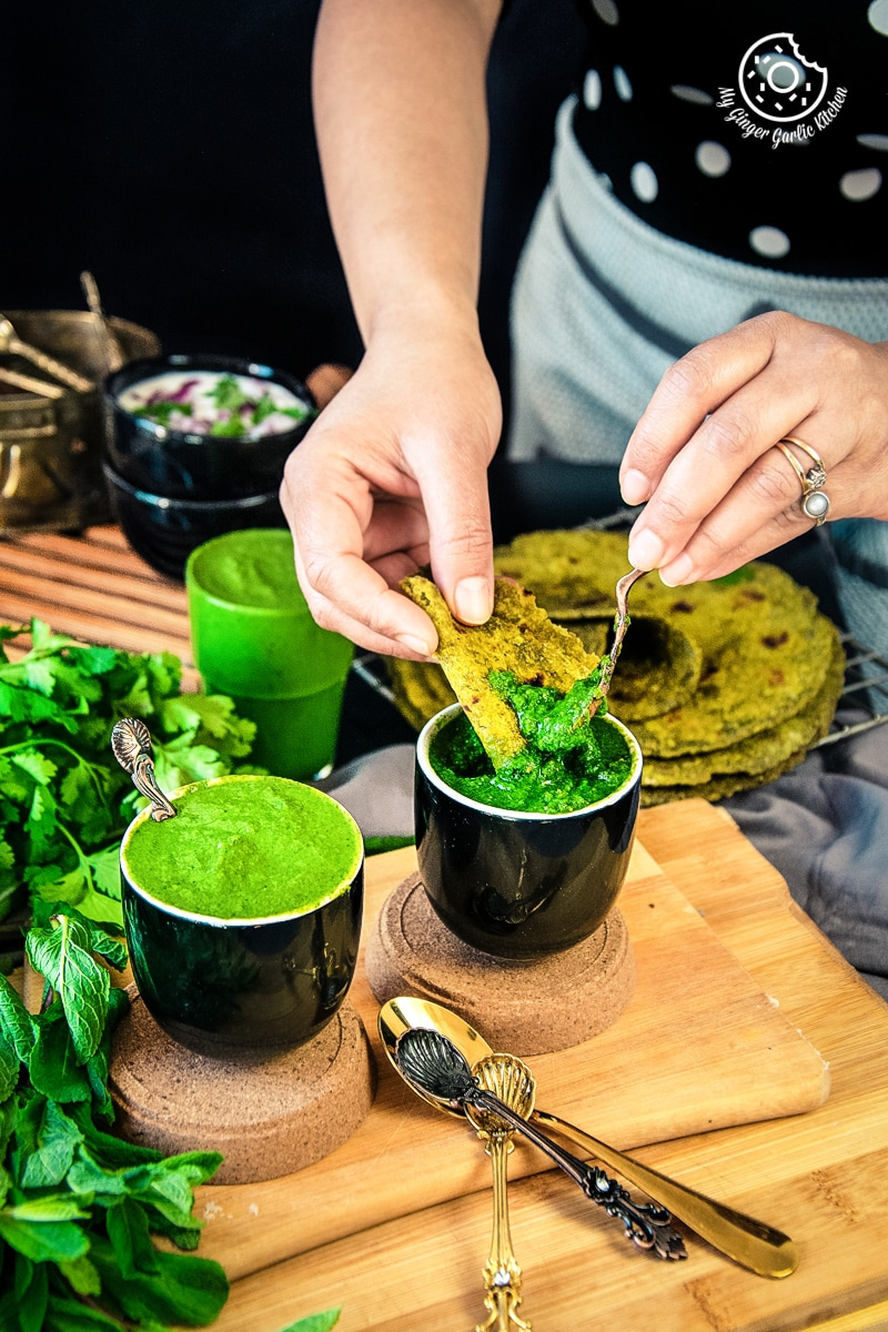 a female dipping flatbread into mint coriander chutneys served in a black ceramic bowl