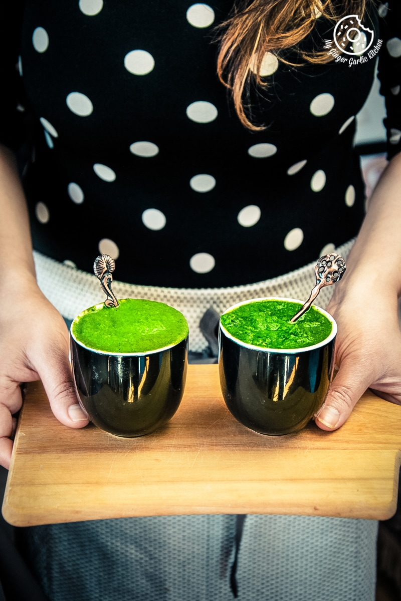 a female holding mint coriander chutney served in black ceramic bowls