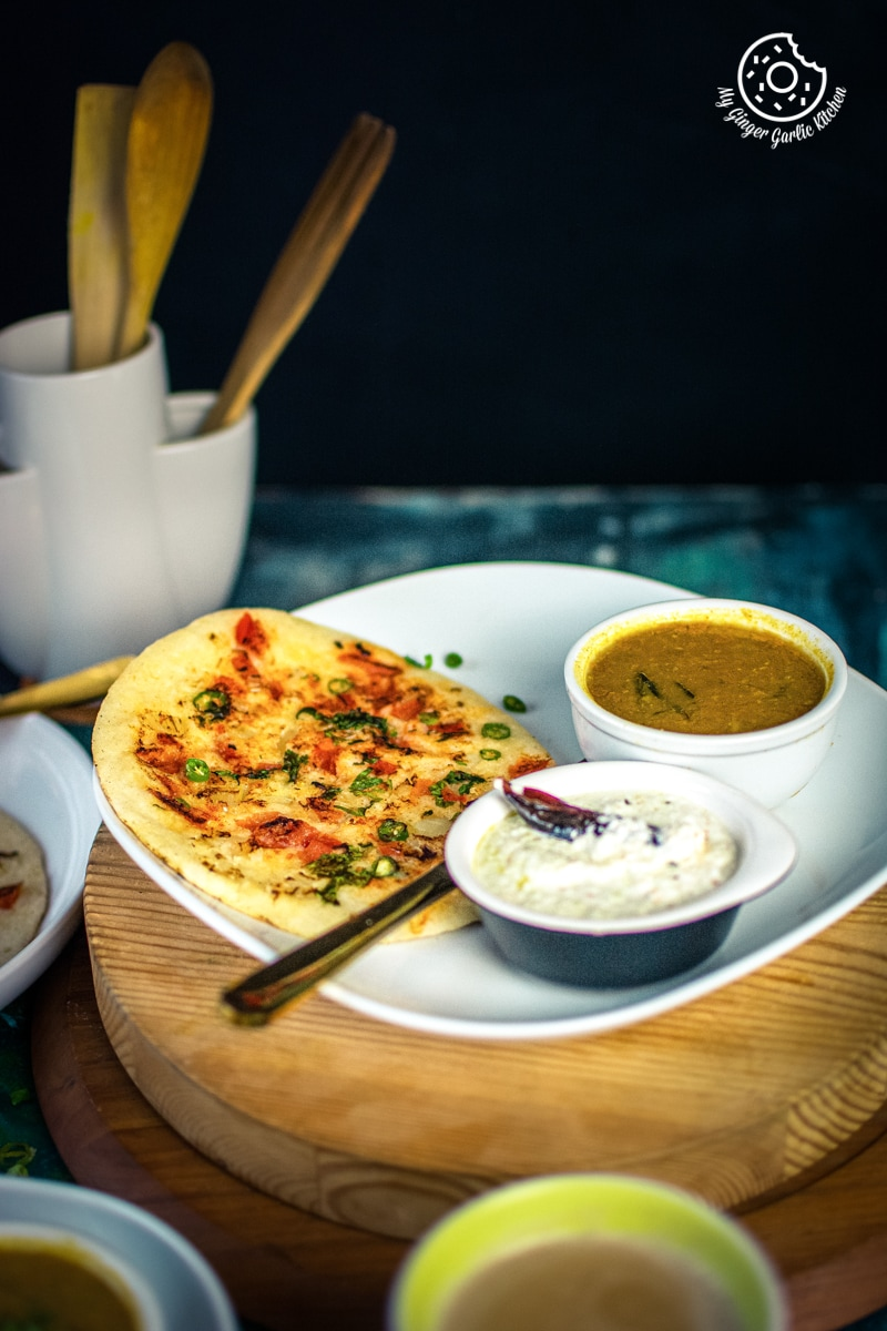 instant rava uttapam served in a white plate with sambar and coconut chutney
