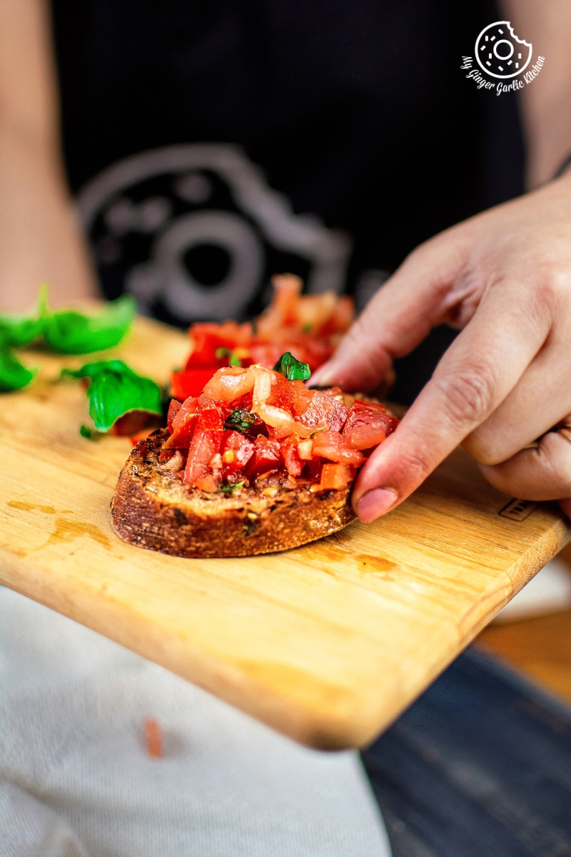 a hand holding tomato bruschetta served on a wooeden board