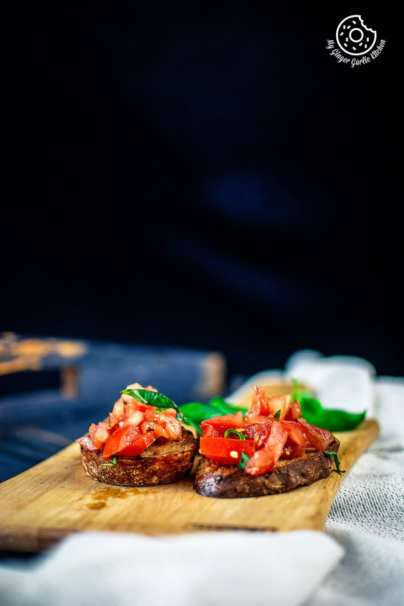 overhead shot of tomato bruschetta served in a white oval shaped plate