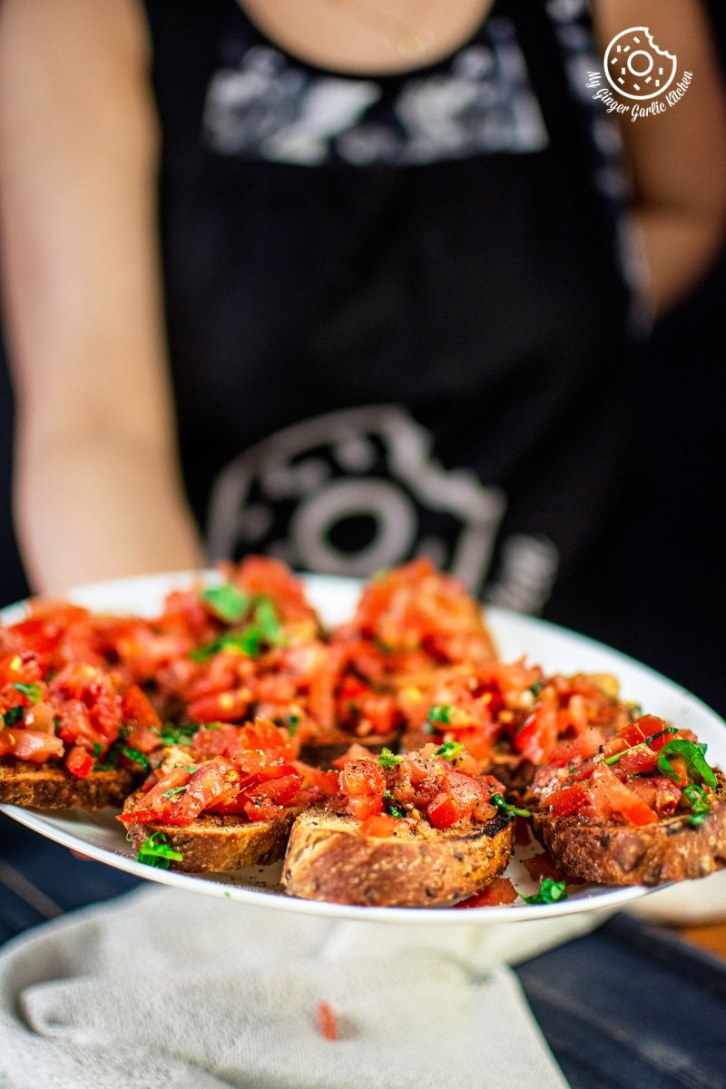 a female holding a plate of tomato bruschetta