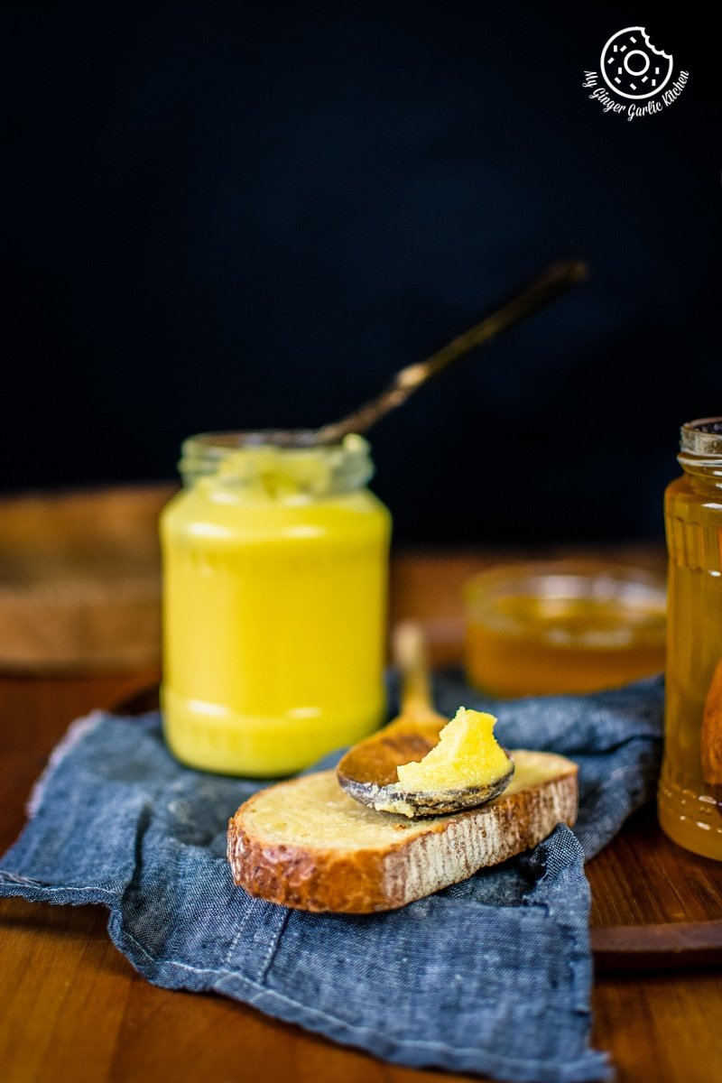 ghee in a glass jar and a wooden spoon