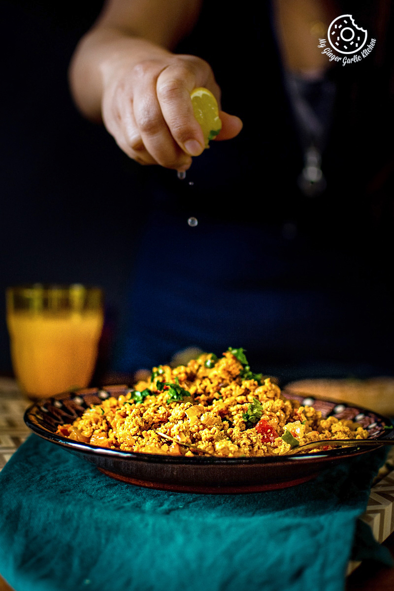 egg bhurji served in a brown plate along with ornage juice