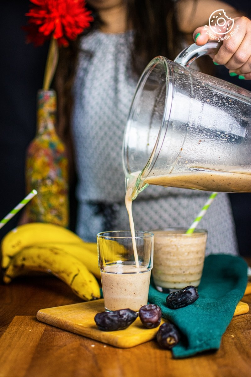 a female pouring banana date smoothie to a glass