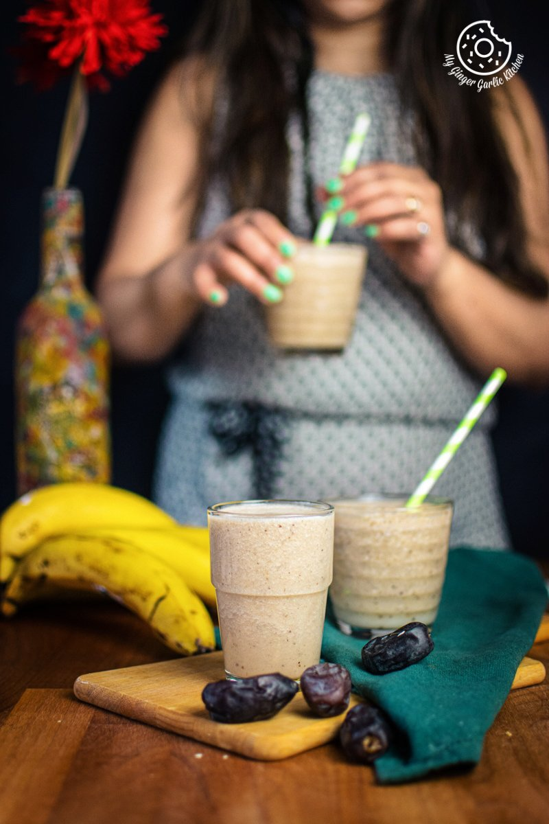 a female holding banana date smoothie glass