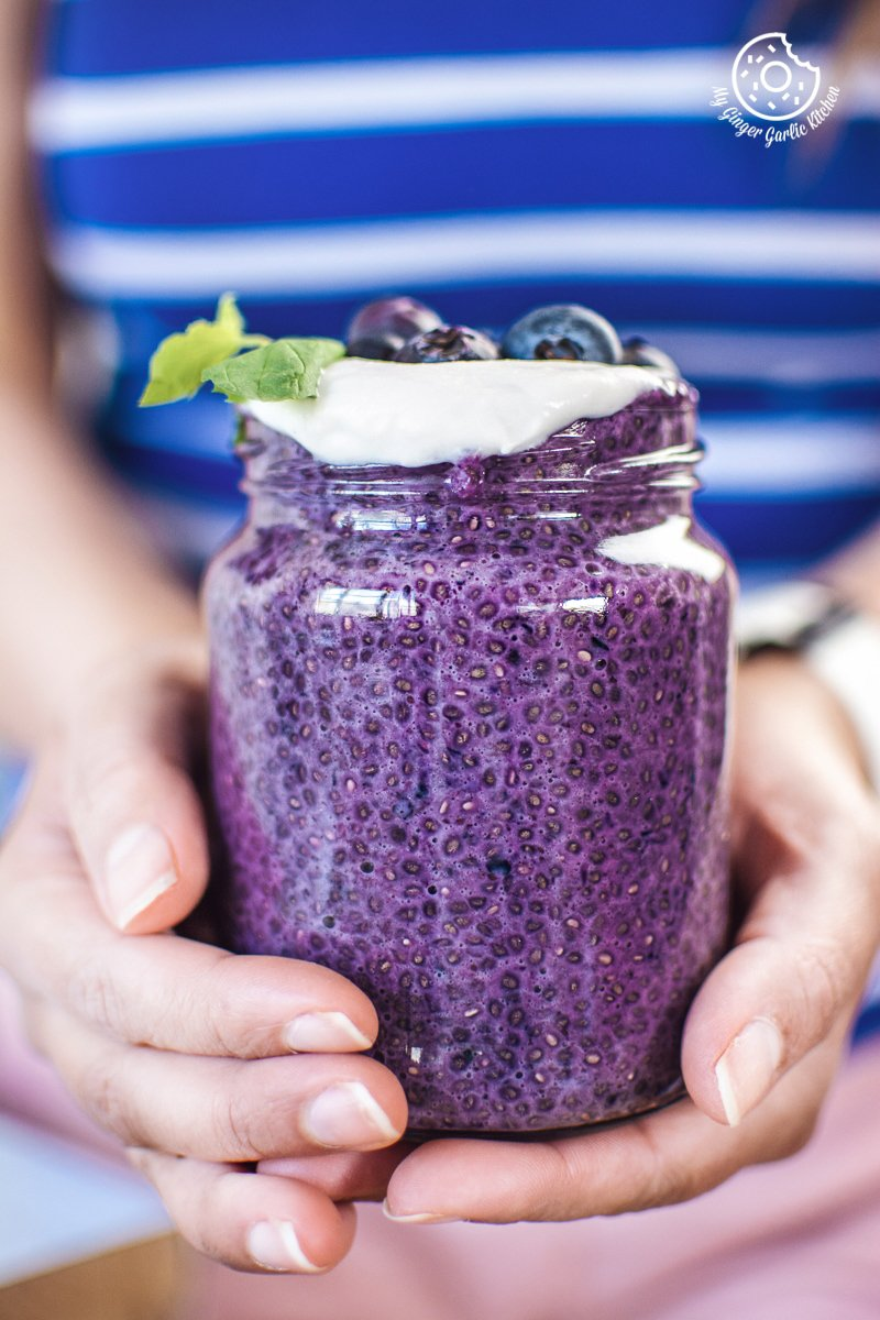 a girl holding bluberry chia seed pudding jar