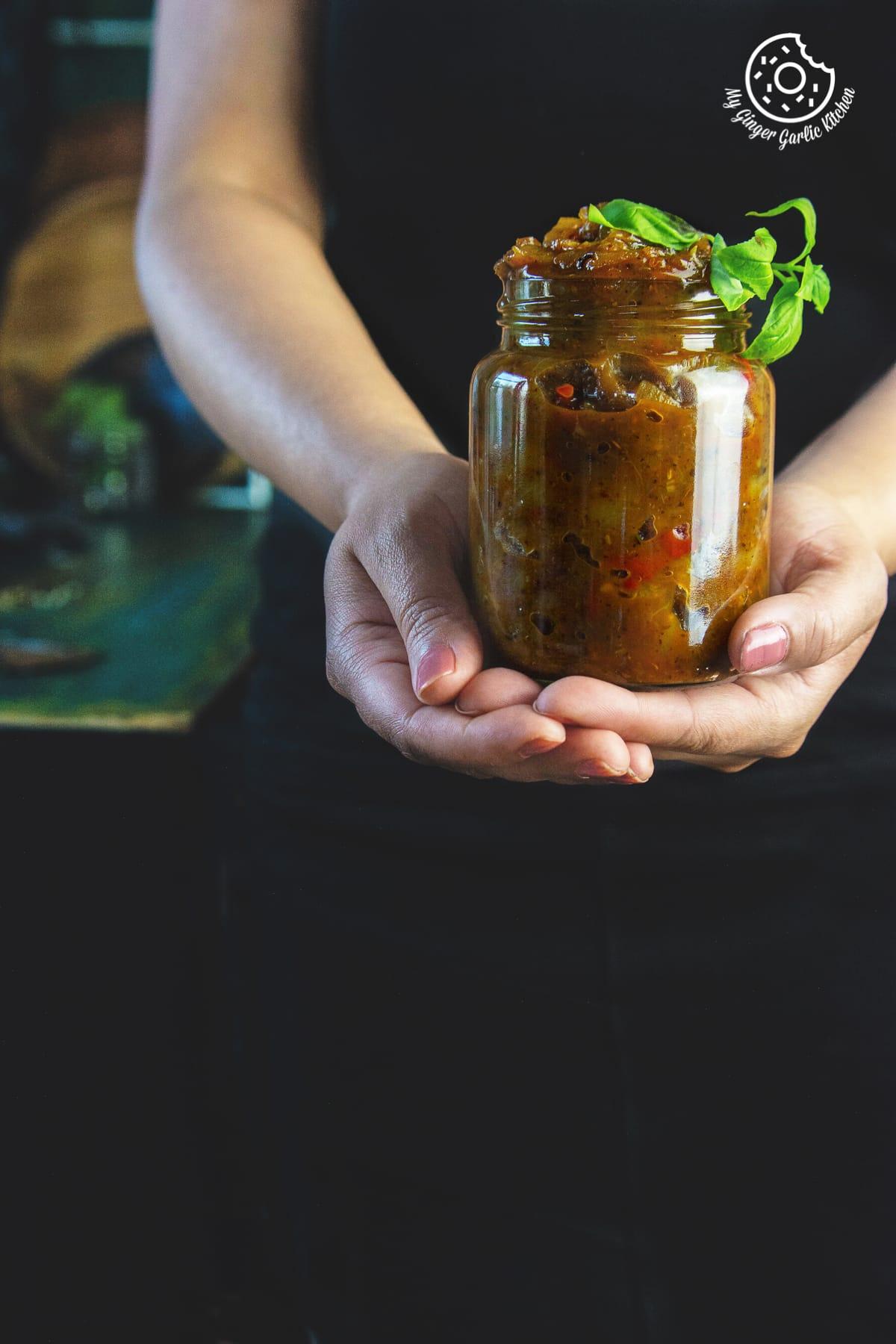 a female is holding peach chutney jar