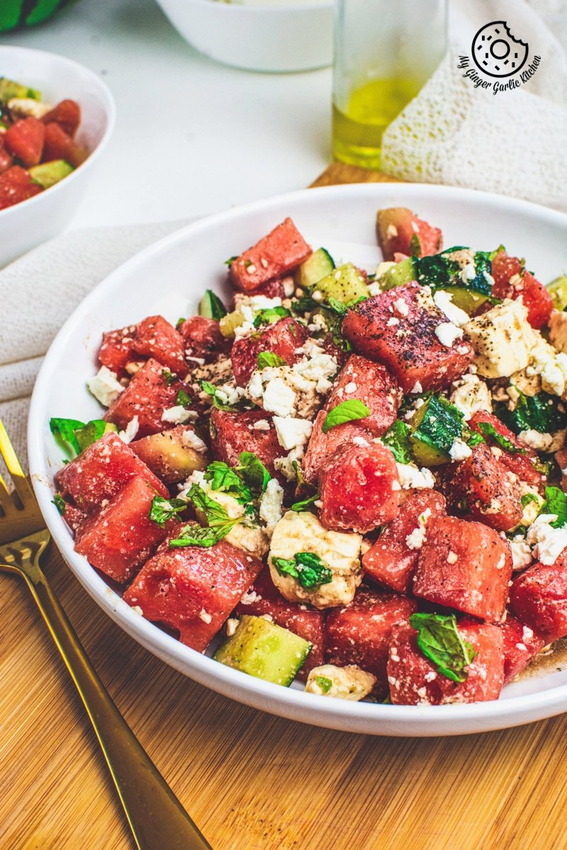Watermelon Cucumber Feta Salad on white plate with golden serving spoons