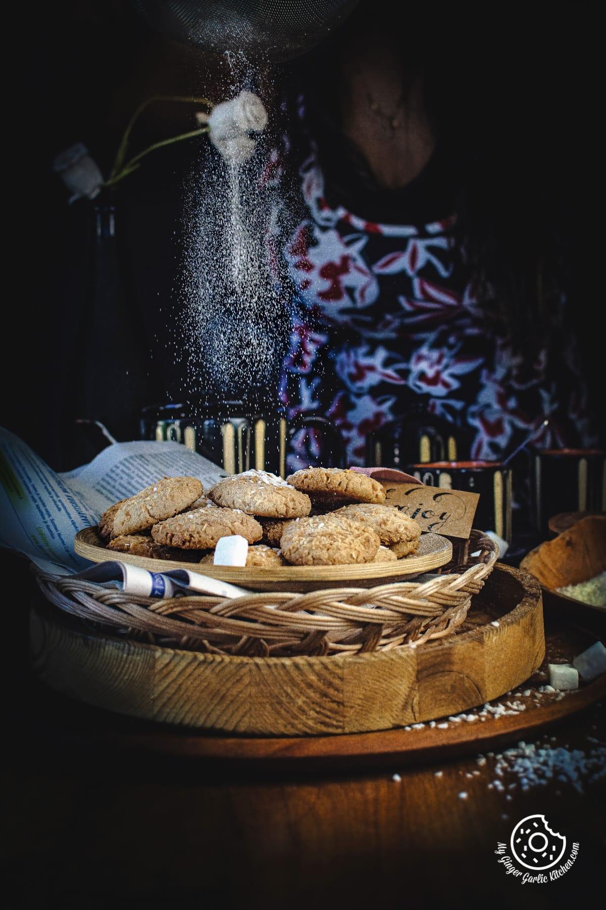 a female sprinkling sugar on coconut cookies