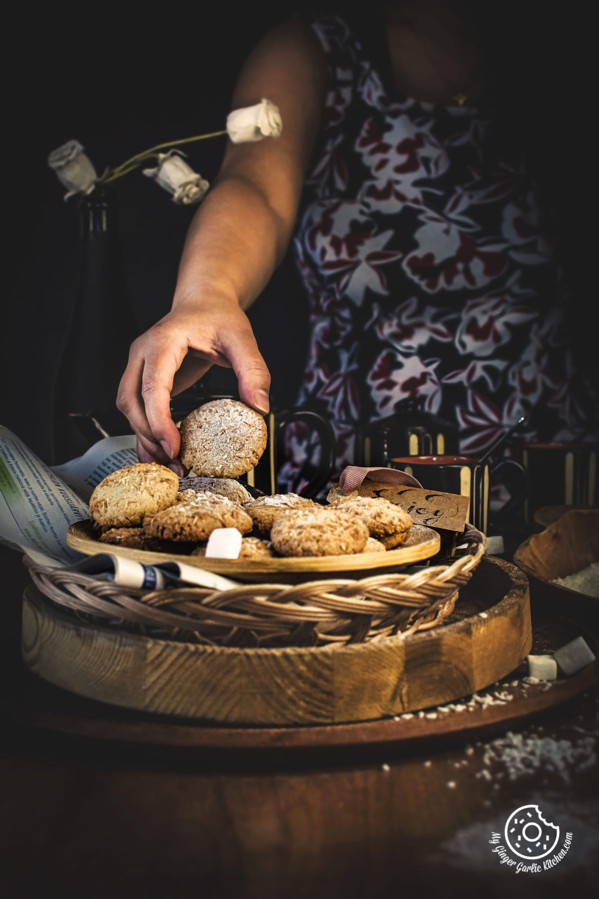 a hand is picking coconut cookie from the plate