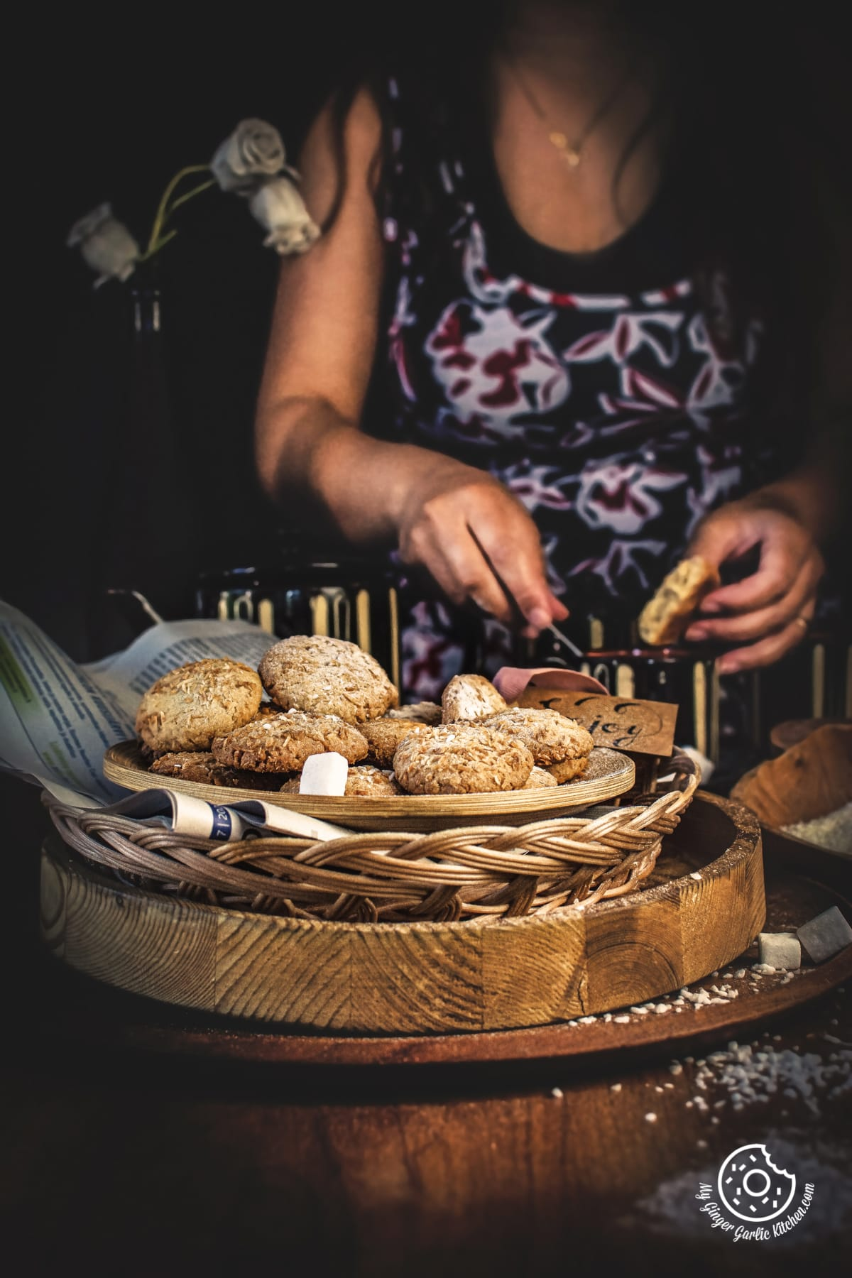 coconut cookies in a wooden plate and a female in the background