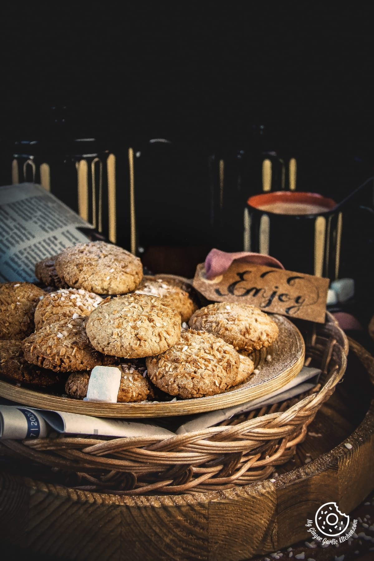 coconut cookies in a plate and black coffee mugs in the background