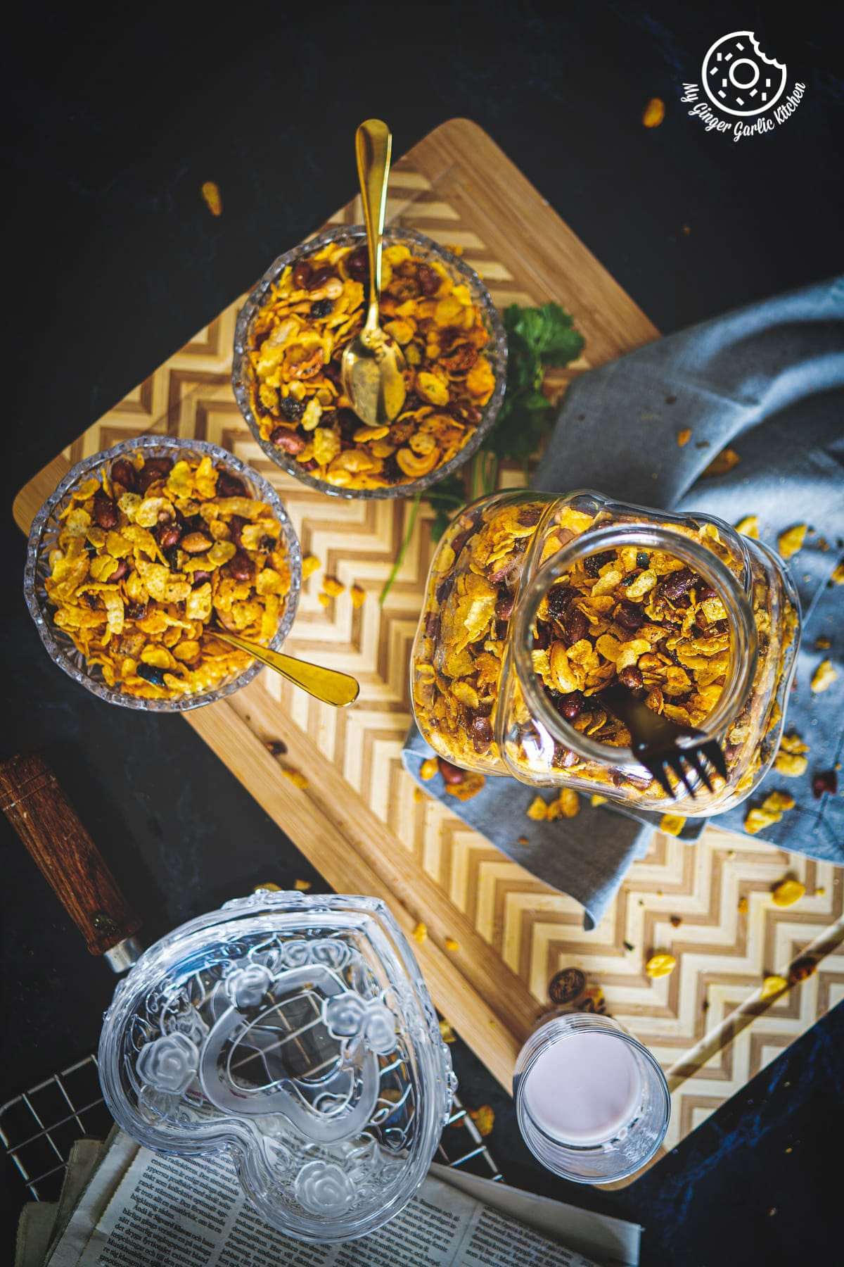 overhead shot of roasted cornflakes chivda in a jar and transparent bowls