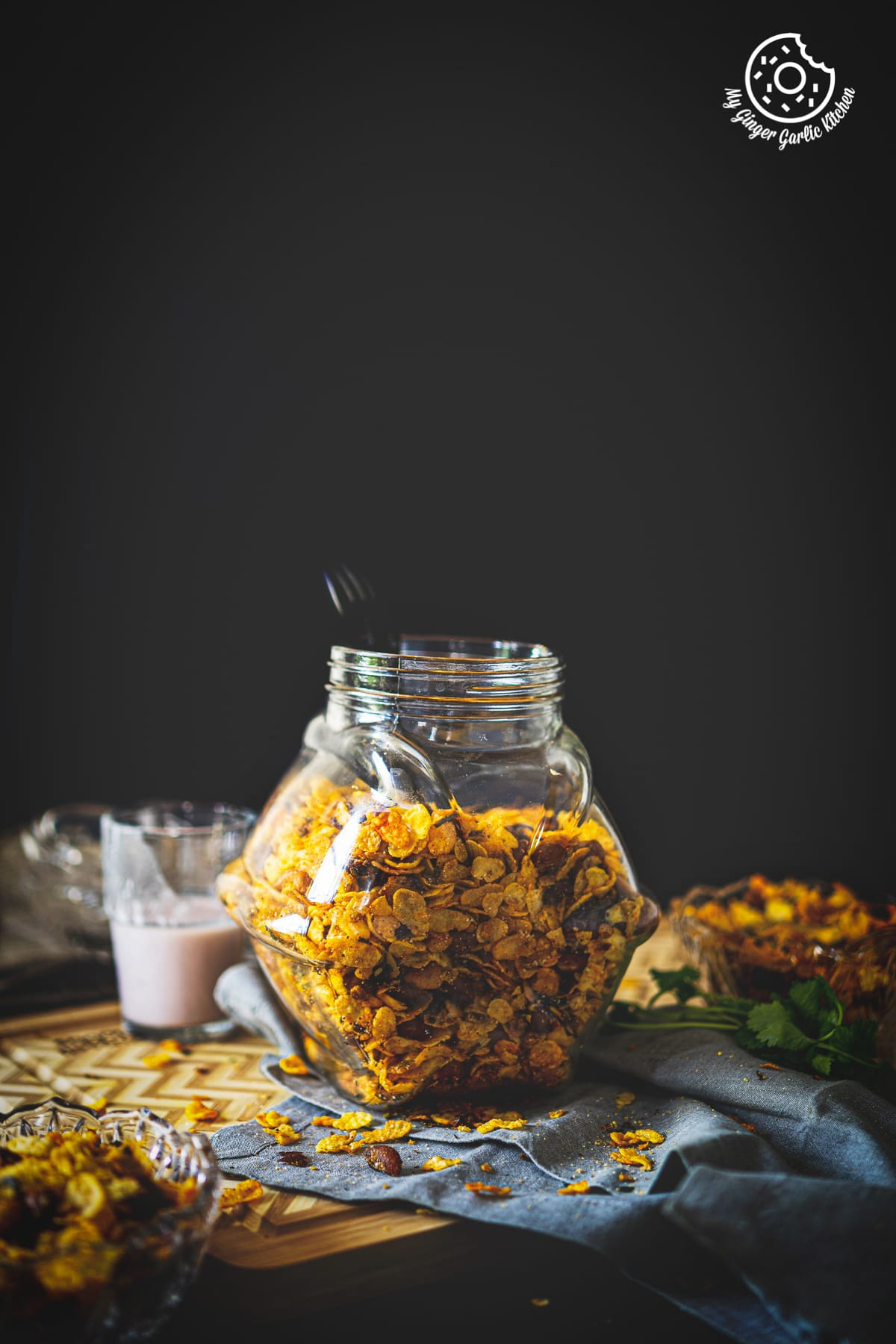 a jar of roasted cornflakes chivda namkeen kept on a wooden board
