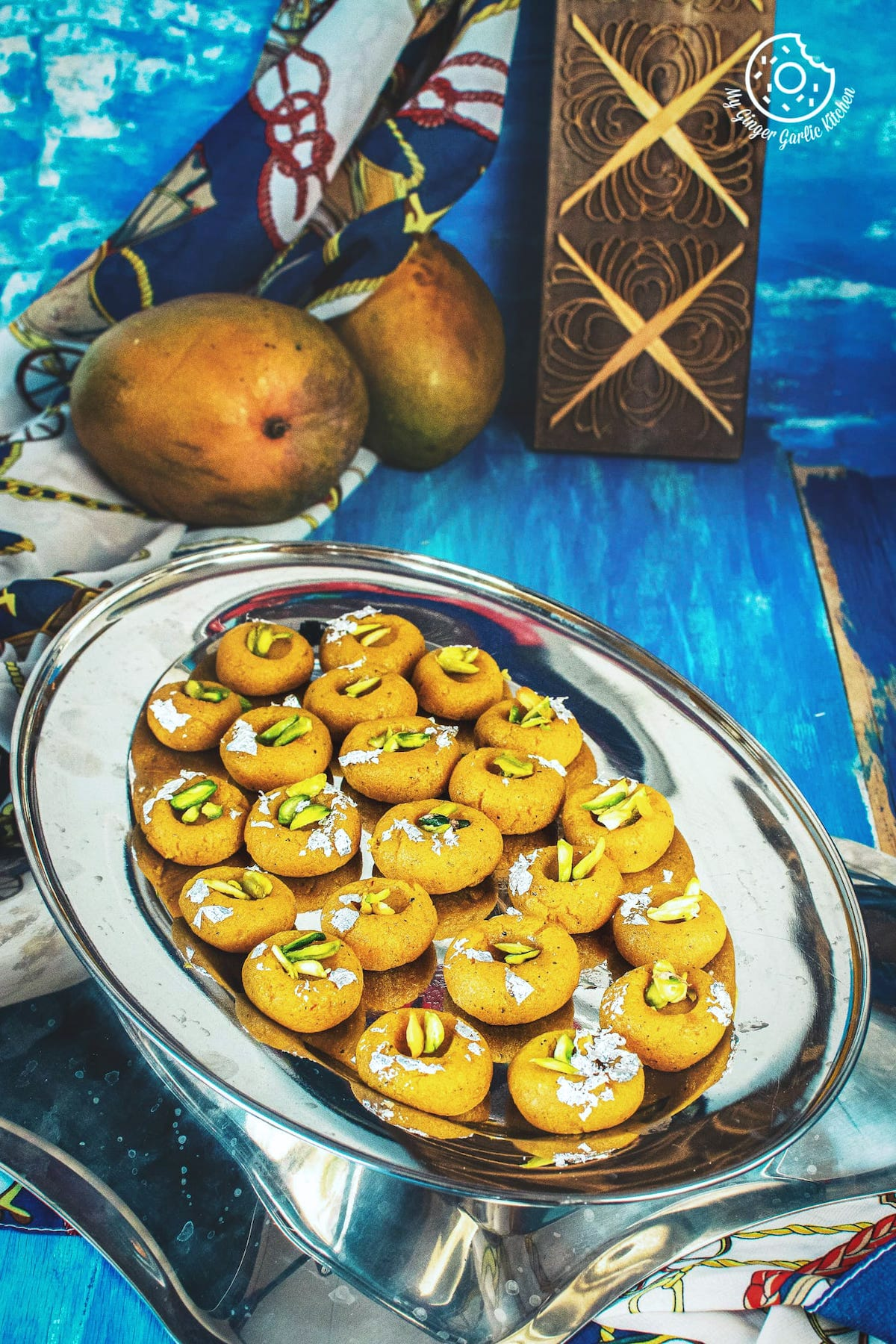 mango peda edible sliver leaves and pistachios served in a steel tray