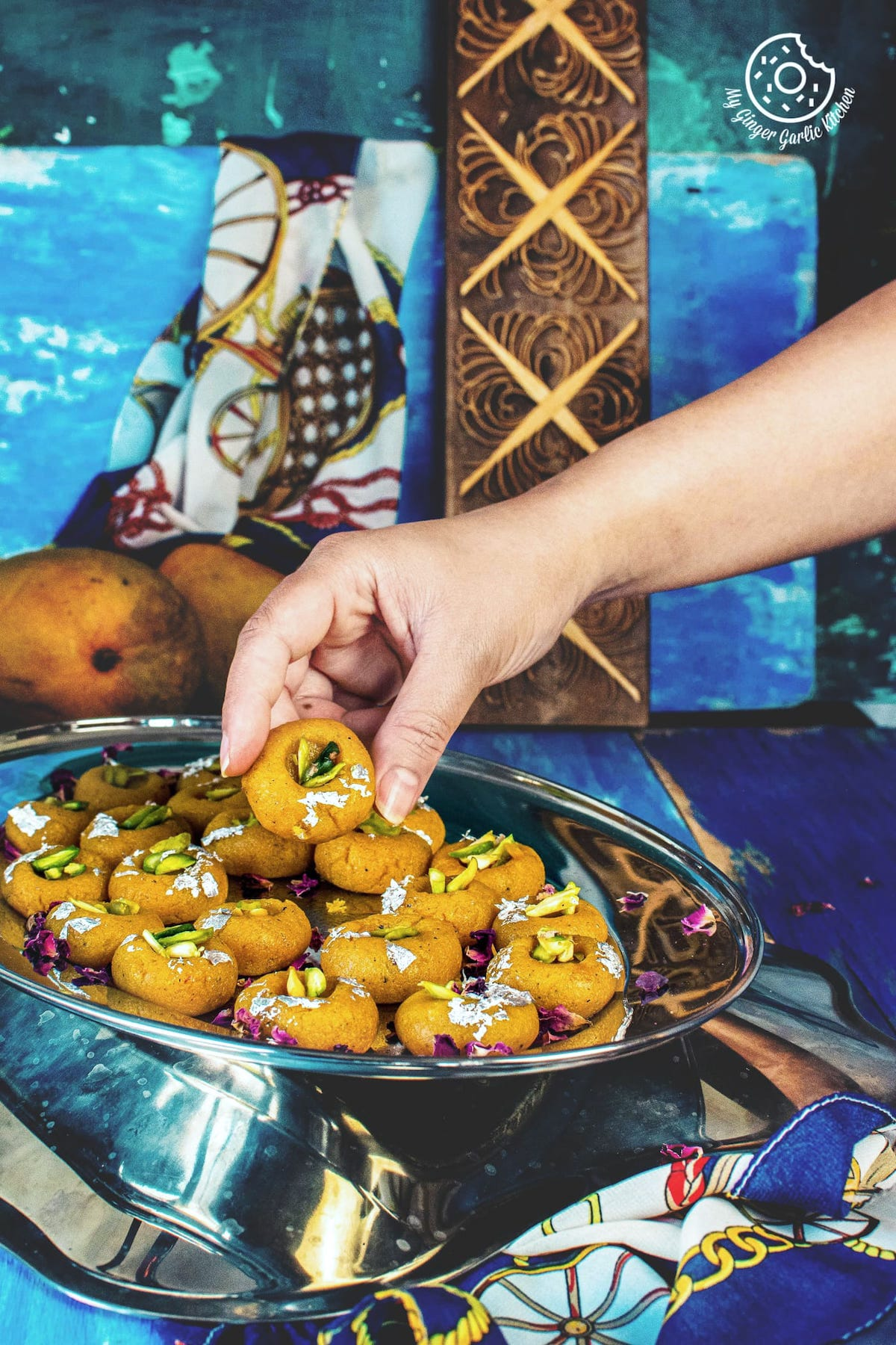a hand holding mango peda served in a steel tray