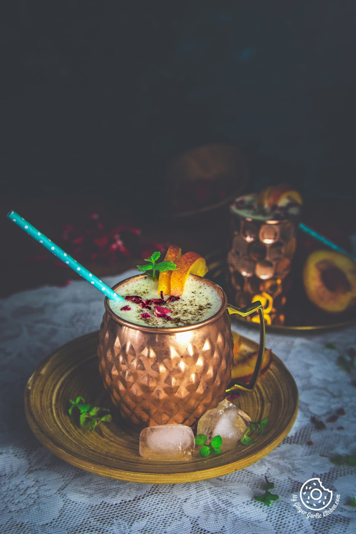 peach lassi decorated with dried rose petals served in a copper mug